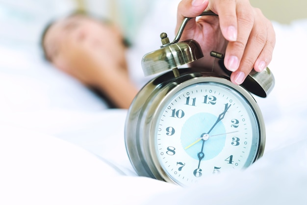 Sleepy young woman in bed with eyes closed extending hand to alarm clock