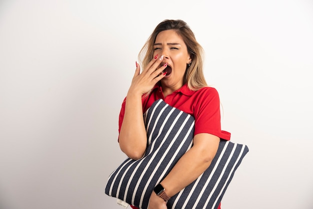 La giovane donna sonnolenta che abbraccia il suo cuscino su imbianca il fondo. Foto Gratuite