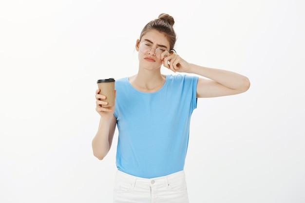 Сонная молодая женщина в очках пьет кофе и устала протирать глаза