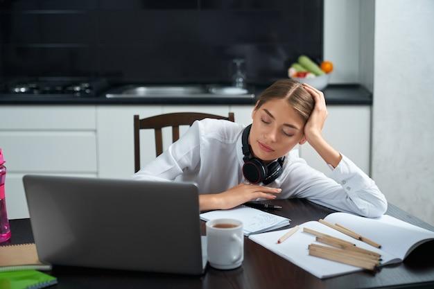Сонная молодая женщина в белой рубашке сидит за столом с открытым ноутбуком и дремлет