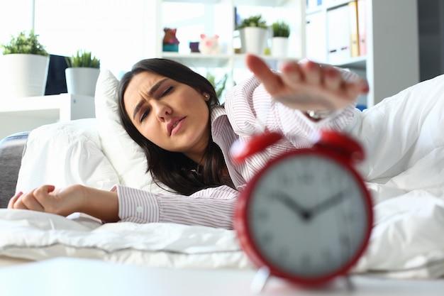 하나의 열린 된 눈 킬 알람 시계를 시도 졸린 젊은 여자의 초상화.