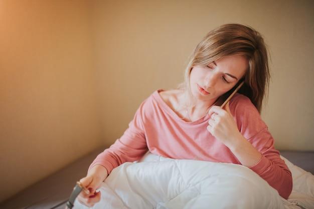 アラームで目を覚ます眠そうな若い女性。彼女は寝坊して仕事をした
