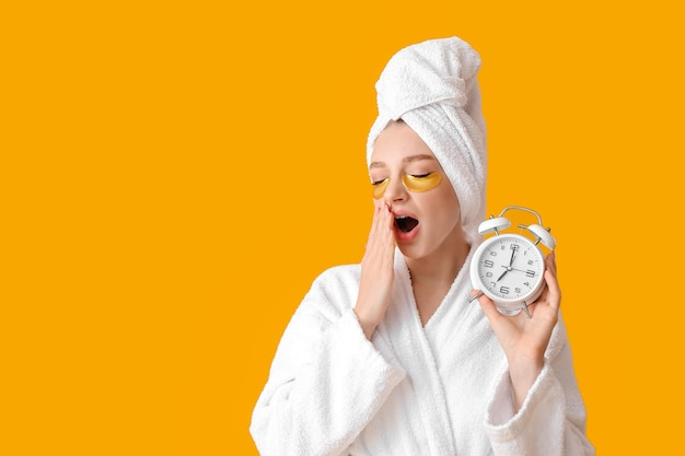 Sleepy young woman with alarm clock on color surface