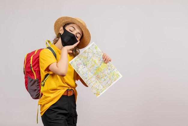 灰色の地図を持ってバックパックを持つ眠そうな若い女性
