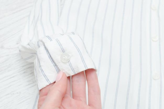 Рукав белой рубашки в полоску в женской руке. детали. модная концепция
