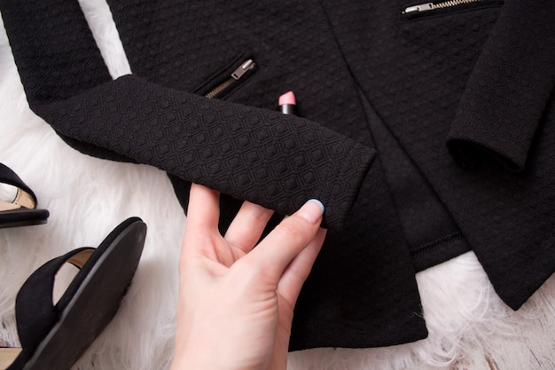 Sleeve of a black jacket in a woman's hand, fashion concept, top view