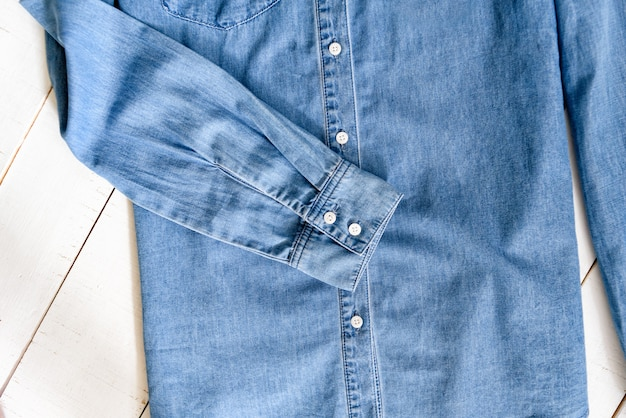 Sleeve of blue denim shirt. clothes concept. details of shirt on wooden background.