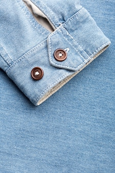 Sleeve of jean cardigan with two plastic buttons against jeans