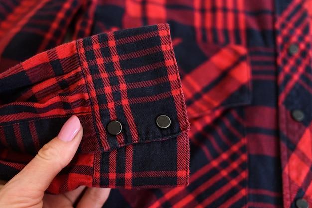 Рукав красной клетчатой рубашки в женской руке. крупный план. мода
