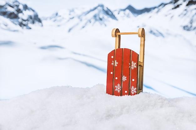 雪山の前の雪の吹きだまりのそり冬のクリスマスの表面
