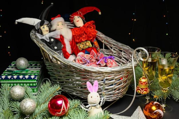 おもちゃ、ベル、クリスマスボール、サンタクロースのそり。黒の背景にクリスマスと新年のコンセプト。
