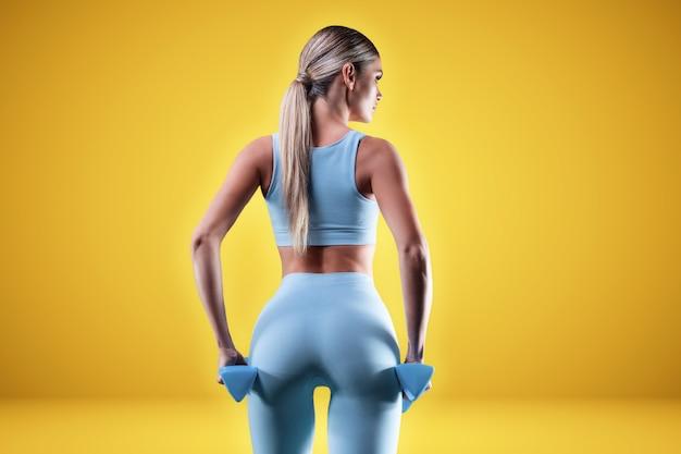 Стройная спортивная девушка в голубых трико позирует с гантелями. вид сзади.