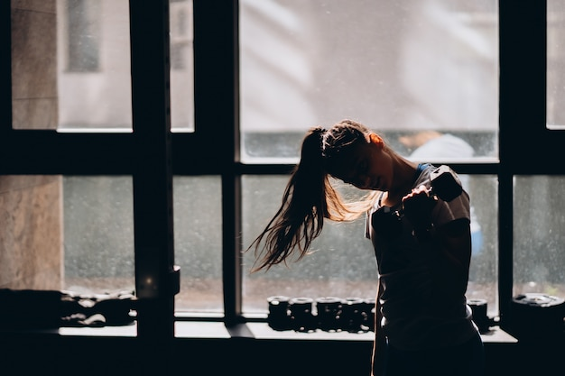 날씬한 운동 소녀 아령으로 운동을 수행합니다.