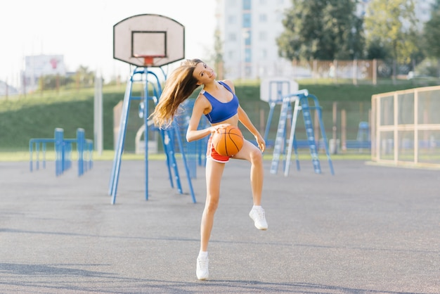 Slender athletic girl in short shots and top plays with a basketball on the playground