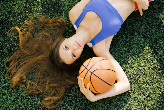 A slender athletic girl with long hair lies on a green lawn and holds a basketball in her hand.