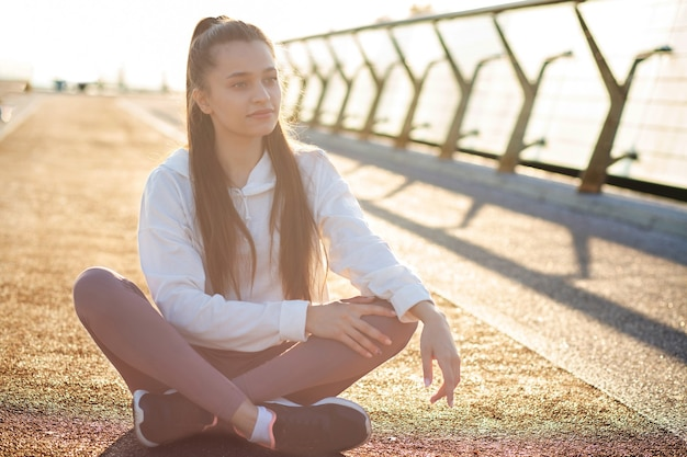 Slender athletic woman with long hair resting after workout at the bridge. space for text, sport concept