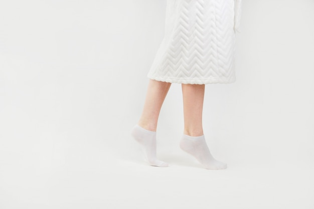 Slender beautiful female legs in socks walking on tiptoe, side view, isolated on white background.