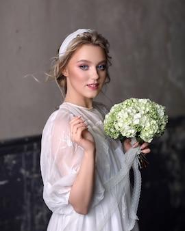 スタジオでヴィンテージのウェディングドレスでほっそりした美しい少女。彼女の手に白い花束を持つ花嫁の肖像画。