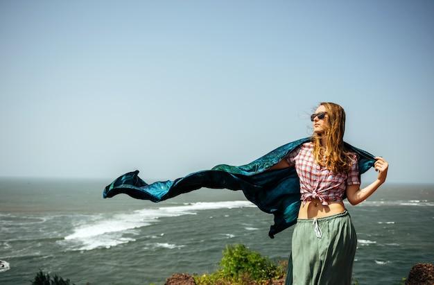 Slender beautiful woman girl on sea rock with pareo shawl