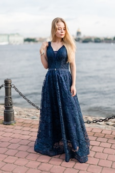 Slender blonde girl in elegant dark-blue floor-length dress on embankment mysteriously looked down.