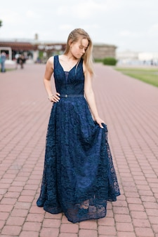 Slender blonde girl touching hem of elegant dark-blue floor-length dress on the pavement.