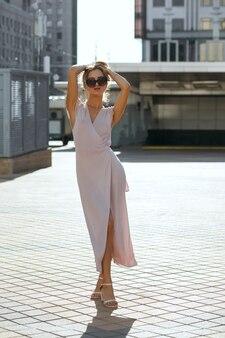 해질녘 거리를 걷고 있는 긴 핑크색 드레스를 입은 날씬한 금발의 여성