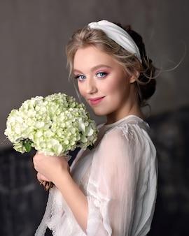 スタジオでヴィンテージのウェディングドレスの細い花嫁。彼女の手でウェディングブーケを持つ微笑んでいる女の子の肖像画