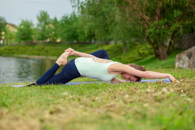 Slender caucasian brunette girl doing yoga in summer on a green lawn by the river