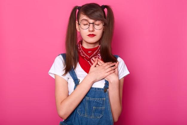 Стройная обаятельная девушка с закрытыми глазами стоит прямо, скрестив обе руки на груди, стараясь почувствовать сердцебиение, выглядит мирно и спокойно. молодость, стиль и эмоции. скопируйте место для рекламы.