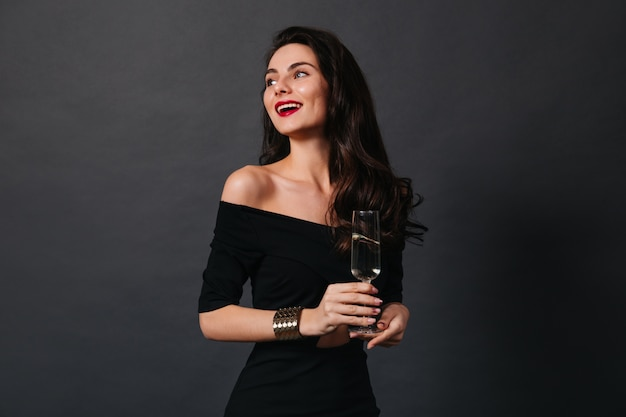Slender dark-haired lady in small black dress and stylish gold bracelet smiles while holding glass of wine on isolated background.