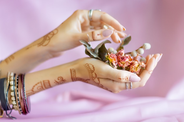 Slender elegant female wrists painted with traditional indian oriental mehndi ornaments by henna. hands dressed in bracelets and rings hold dry roses flowers. pink fabric with folds on background.