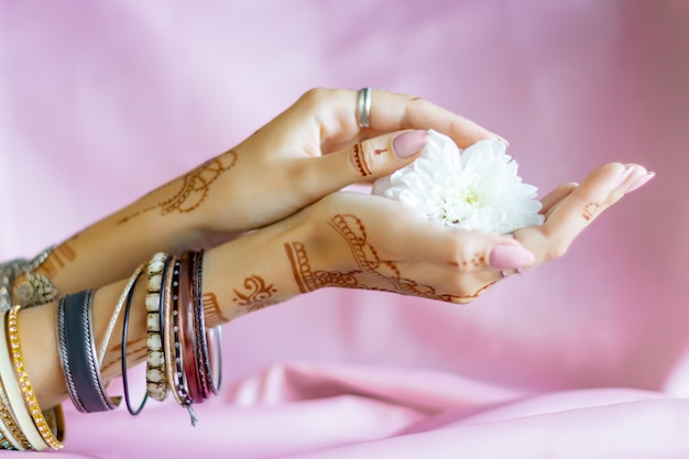 Slender elegant female wrists painted with traditional indian oriental mehndi ornaments by henna. hands dressed in bracelets and rings hold white flower. light pink fabric with folds on background.
