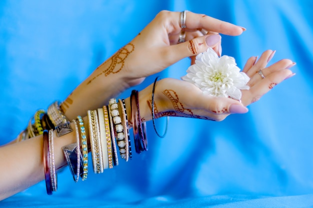 Slender elegant female wrists painted with traditional indian oriental mehndi ornaments by henna. hands dressed in bracelets and rings hold white flower. sky blue fabric with folds on background.