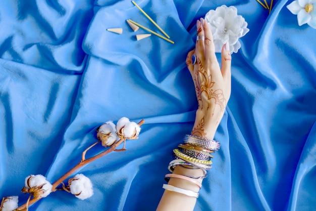 ヘナによってインドの東洋の一時的な刺青の装飾品で描かれた細い女性の手。ブレスレットとリングに身を包んだ手は白い花を持っています。ひだと背景に綿の枝を持つ青い布。