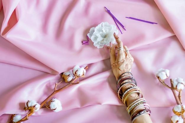 Стройная женская рука, расписанная хной индийскими восточными орнаментами менди. рука, одетая в браслеты и кольца, держит белый цветок. светло-розовая ткань со складками и хлопковыми ветвями на фоне.