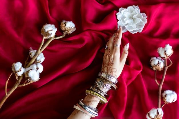 ヘナによってインドの東洋の一時的な刺青の装飾品で描かれた細い女性の手。ブレスレットに身を包んだ手は白い花を持っています。ひだと背景に綿の枝のあずき色の生地。