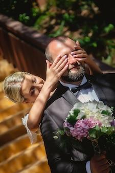 ウェディングドレスのほっそりした女性は、ウェディングブーケで新郎の目を閉じます。美しい結婚式の朝。セレクティブフォーカス。対角線の画像。素晴らしい女の子。女性は感情を示します。青い目をした金髪