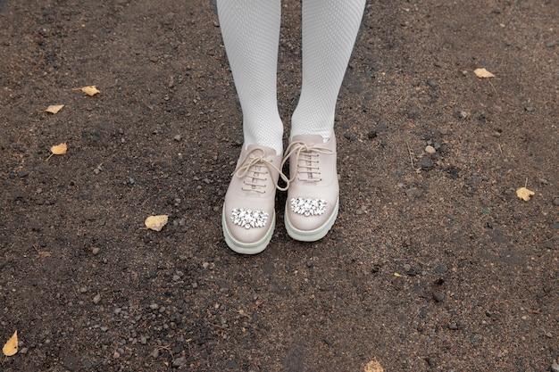 黒い地面に明るいタイツと明るい色のレースアップシューズの細い女性の脚。ラインストーン。ホワイトソール。今シーズンの秋の靴のコンセプト。写真。スペースをコピーします。上面図