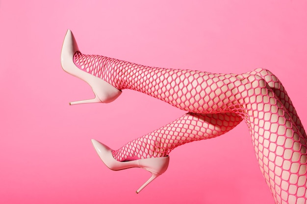 Slender female legs raised in sexy pink fishnets and matching high heels