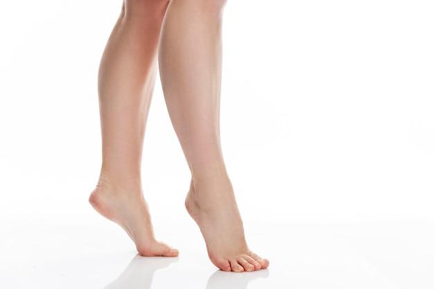 膝までの細い女性の脚。美容と健康。白い背景で隔離。テキスト用のスペース。