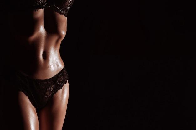 검은 배경에 속옷에 여자의 날씬한 그림. 텍스트 복사 공간을 가진 젊은 여자의 운동 몸