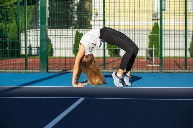 테니스 코트에서 운동하기 전에 스트레칭을 하는 날씬한 금발의 여성, 야외 촬영