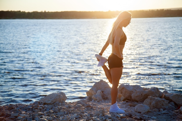 Slender fit woman on rocky beach stretching after workout. sporty girl doing exercises on sunset or sunrise.