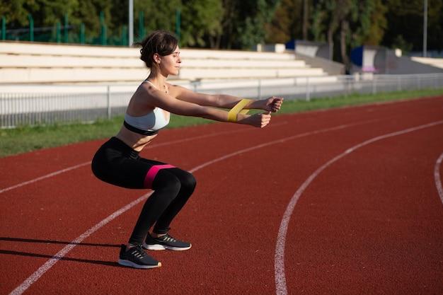 スタジアムで屋外の輪ゴムでスクワットをしている細いフィットネス女性。空きスペース