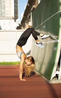 태양 광선에 테니스 코트에서 포즈를 취하는 스포츠 옷을 입고 완벽한 몸을 가진 날씬한 피트니스 여성