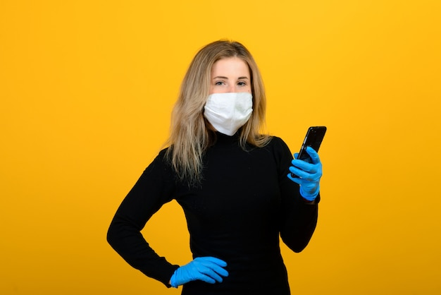 A slender girl in a black bodysuit and medical mask from viruses poses