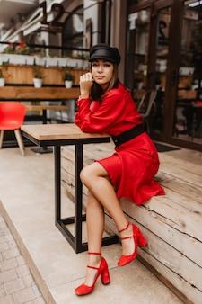 Ragazza snella in scarpe eleganti e vestito con cintura seduto nella caffetteria. ritratto di giovane donna che osserva minuziosamente