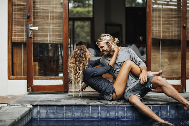 날씬한 소녀는 사랑하는 남자 친구를 안고 사랑으로 그를 바라 봅니다. 남자와여자가 수영장에서 휴식