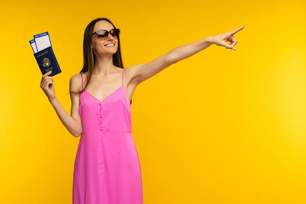 Стройная девушка в розовом платье и солнечных очках держит паспорт с авиабилетом и указывает
