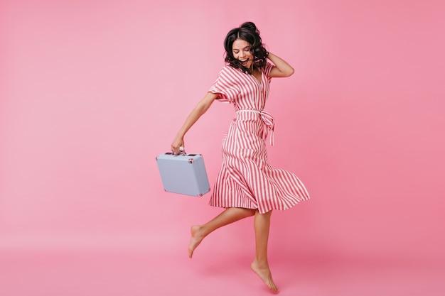 멋진 분위기의 날씬한 소녀는 재미 있고 손에 가방을 들고 춤을 추고 있습니다. 랩 드레스에서 이탈리아 모델의 샷입니다.